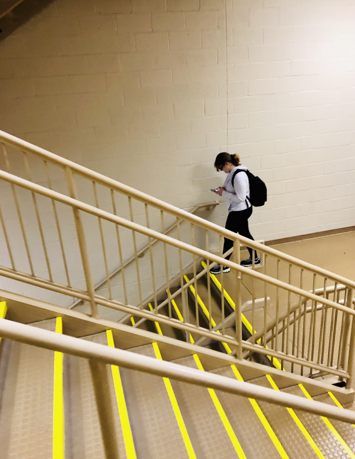 A Monroe-Woodbury High School student gazes intently at her phone as she walks down the stairs. Students are frequently seen so engaged in their electronics that they bump into others or trip while walking to their next class in the hallways of MWHS.